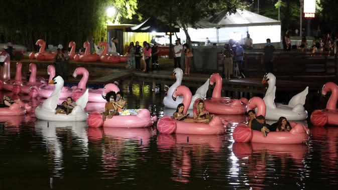 Orang-orang bersantai di atas balon flamingo saat mereka menonton film selama Festival Terapung pertama di Danau Sarah Kubstichek Brasilia, Brasil (30/9/2020). Warga bisa duduk santai di balon karet menonton film dan matahari terbenam di festival ini. (AP Photo/Eraldo Peres)