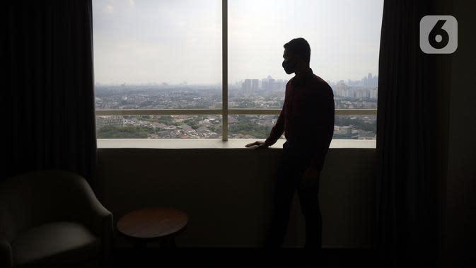 Pengunjung memandang keluar jendela kamar Hotel Grand Whiz Poins Simatupang, Jakarta, Kamis (16/04/2020). Di tengah pandemi virus corona COVID-19, hotel ini menyediakan paket isolasi mandiri selama 14 hari dengan harga Rp 6.500.000. (merdeka.com/Dwi Narwoko)