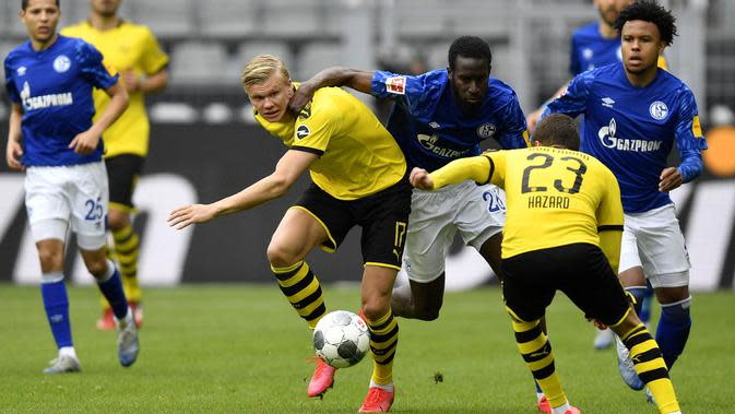 Penyerang Borussia Dortmund, Erling Haaland, berusaha melewati pemain Schalke 04 pada laga Bundesliga di Stadion Signal Iduna Park, Sabtu (16/5/2020). Dortmund menang 4-0 atas Schalke 04. (AP/Martin Meissner)