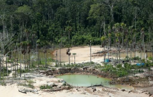 """President Bolsonaro has said he could pull Brazil from the Paris Climate Accord, following Trump's lead. Aerial view taken on March 5, 2019 of the deforestation surrounding a dismantled gold digging system, near the illegal gold miners' camp """"Mega 12"""", in the Amazon jungle in the Madre de Dios region, southeastern Peru, during a police operation to destroy illegal machinery and equipment.Illegal gold mining in the Amazon has reached """"epidemic"""" proportions in recent years, causing damage to pristine forest and waterways and threatening indigenous communities"""