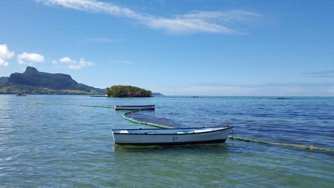 Penghalang digunakan untuk menampung tumpahan minyak yang mencemari lepas pantai tenggara Mauritius di Mahebourg Waterfront, Sabtu (8/8/2020). Mauritius memberlakukan status darurat setelah kapal Jepang, MV Wakashio, kandas dan menumpahkan 1.000 metrik ton minyak mentah. (Sophie Seneque via AP)
