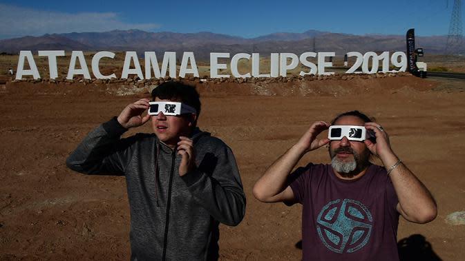 Dua orang pria mencoba kaca mata khusus untuk melihat gerhana matahari total di sebuah kamp astronomi di komune Vallenar di gurun Atacama, Santiago, Chile (1/7/2019). Gerhana matahari total akan terlihat dari Chile dan Argentina pada 2-3 Juli. (AFP Photo/Martin Bernetti)