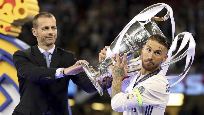 Presiden UEFA, Aleksander Ceferin, memeberikan piala Liga Champion kepada Kapten Real Madrid, Sergio Ramos di Stadion Millennium, Cardiff, (03/06/2017). (AP/Nick Potts)