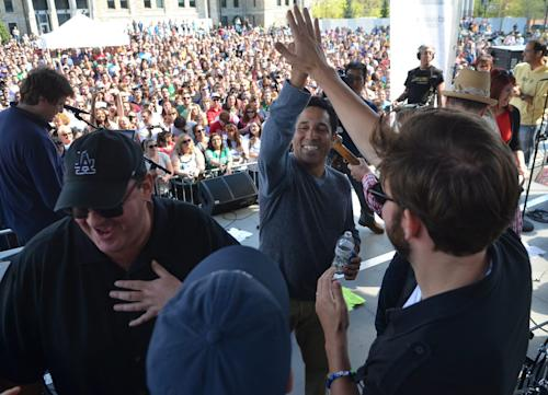 """Actor Oscar Nunez, center, high-fives cast mate John Krasinski after singing on stage during """"The Office"""" Wrap Party, Saturday, May 4, 2013, in Scranton, Pa. The NBC mockumentary about cubicle-dwellers at the fictional Dunder Mifflin wraps up May 16, and thousands attended the """"Wrap Party"""" on Saturday. (AP Photo/Scranton Times & Tribune, Jason Farmer)"""