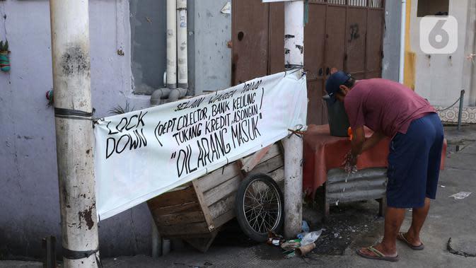 Warga mencuci tangan sebelum masuk salah satu gang yang ditutup secara mandiri di kawasan Tambora, Jakarta, Sabtu (4/4/2020). Penutupan akses masuk kawasan ini untuk membatasi kegiatan warga dan mencegah penyebaran serta penularan virus COVID-19. (Liputan6.com/Helmi Fithriansyah)