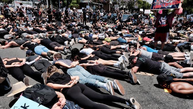 Anggota komunitas LGBTQ bersama pengunjuk rasa Black Lives Matter melakukan aksi tiarap di jalan dengan tangan seolah terikat di West Hollywood, California, Rabu (3/6/2020). Aksi menyimbolkan momen terakhir George Floyd saat lehernya ditindih lutut polisi Minneapolis pada 25 Mei. (AP/Richard Vogel)
