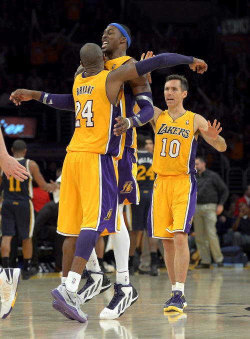 Los Angeles Lakers guard Kobe Bryant, left, and center Dwight Howard, center, celebrates along with guard Steve Nash during the second half of their NBA basketball game against the Utah Jazz, Friday, Jan. 25, 2013, in Los Angeles. The Lakers won 102-84. (AP Photo/Mark J. Terrill)