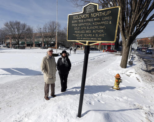 """David Fiske, left, and Rachel Seligman, two of the co-authors of """"Solomon Northup: The Complete Story of the Author of Twelve Years a Slave,"""" pose at the Solomon Northup historical marker on Thursday, March 13, 2014, in Saratoga Springs, N.Y. (AP Photo/Mike Groll)"""