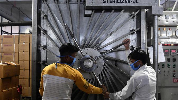 Para pekerja mengunci pintu ruang sterilisasi di pabrik Jarum Suntik Hindustan di Faridabad (2/9/2020). Produsen jarum suntik terbesar di India meningkatkan produksinya untuk menghasilkan satu miliar unit. (AFP/Sajjad Hussain)