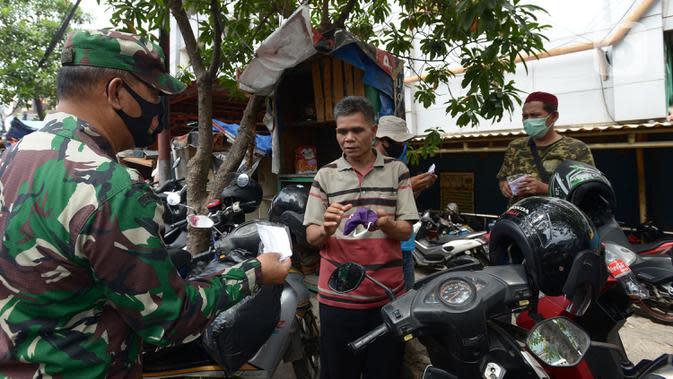 Anggota TNI membagikan masker kepada warga di Pasar Jatinegara, Kamis (10/9/2020). Petugas gabungan terus melakukan himbauan untuk memakai masker dan membagikan masker di pasar tersebut. (merdeka.com/Imam Buhori)