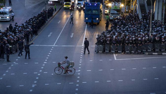 Seorang pria mengendarai sepedanya melewati polisi antihuru-hara yang mengambil posisi di persimpangan menuju Gedung Pemerintah setelah mengejar sekelompok kecil demonstran pro-demokrasi di Bangkok, Thailand, Kamis (15/10/2020). (AP Photo/Gemunu Amarasinghe)
