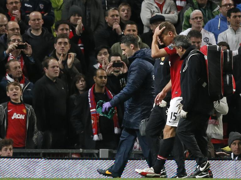 Manchester United's Vidic leaves the field with a head injury during their English Premier League soccer match against Arsenal in Manchester