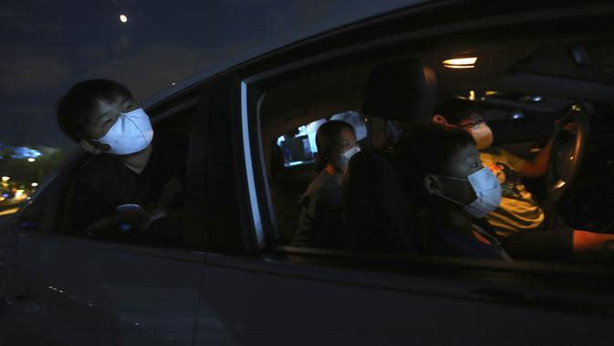 Anggota keluarga di dalam mobil menonton sirkus drive-in dari tempat parkir di Seoul, Korea Selatan, Jumat (25/9/2020). Acara ini digelar untuk memberikan hiburan bagi orang-orang selama wabah virus corona. (AP Photo/Ahn Young-joon)