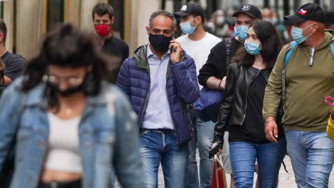Orang-orang memakai masker untuk mencegah penyebaran COVID-19 saat mereka berjalan-jalan di pusat kota Roma pada Sabtu (3/10/2020). Masker wajah harus dipakai setiap saat di luar rumah di ibu kota Italia Roma dan wilayah sekitar Lazio mulai Sabtu, 3 Oktober. (AP Photo/Andrew Medichini)