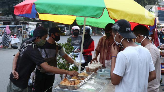 Aktivitas jual beli makanan untuk berbuka puasa di kawasan Bendungan Hilir, Jakarta, Sabtu (25/4/2020). Meski ditengah pandemi virus Covid-19, masyarakat masih antusias berburu penganan berbuka puasa dengan tetap menerapkan pola jaga jarak dan memakai masker. (Liputan6.com/Helmi Fithriansyah)