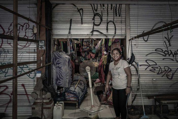 A woman smiles outside her small stall at a market in Kuta, Bali, surrounded by closed and gratified shutters.