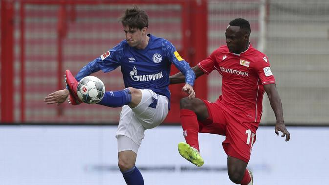 Pemain Union Berlin, Anthony Ujah, berebut bola dengan pemain Schalke, Juan Miranda, pada laga Bundesliga di Weserstadion Minggu (7/6/2020). Kedua tim bermain imbang 1-1. (AP/Michael Sohn)