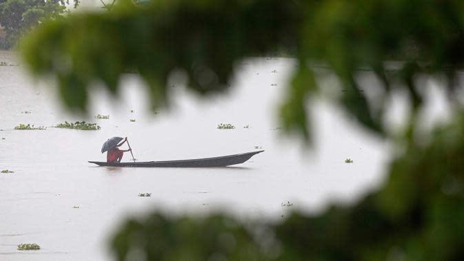 Seorang penduduk desa mengayuh perahunya di atas perairan banjir di distrik Morigaon di Assam, India (26/6/2020). Banjir disebabkan meluapnya Sungai Brahmaputra akibat hujan yang terus turun. (AP Photo/Anupam Nath)