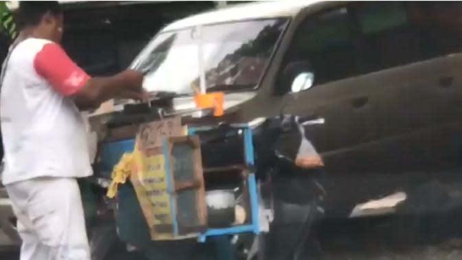 Seorang pedagang ketahuan mencuci wajan masaknya dengan air genangan di jalan