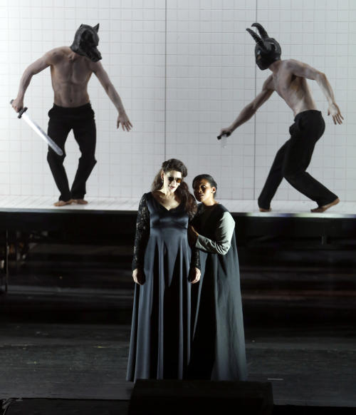 "In this picture taken Friday, June 21, 2013, Anja Harteros in the role of Leonora, left, sings during a dress rehearsal for the opera ""Il Trovatore"" by Giuseppe Verdi in the Bavarian State Opera House in Munich, southern Germany. This wild new production by Olivier Py opened the company's annual Munich Opera Festival. It's a non-stop barrage of nightmarish images mixing styles and periods that assault the audience at lightning speed on a multi-tiered revolving set. (AP Photo/Matthias Schrader)"