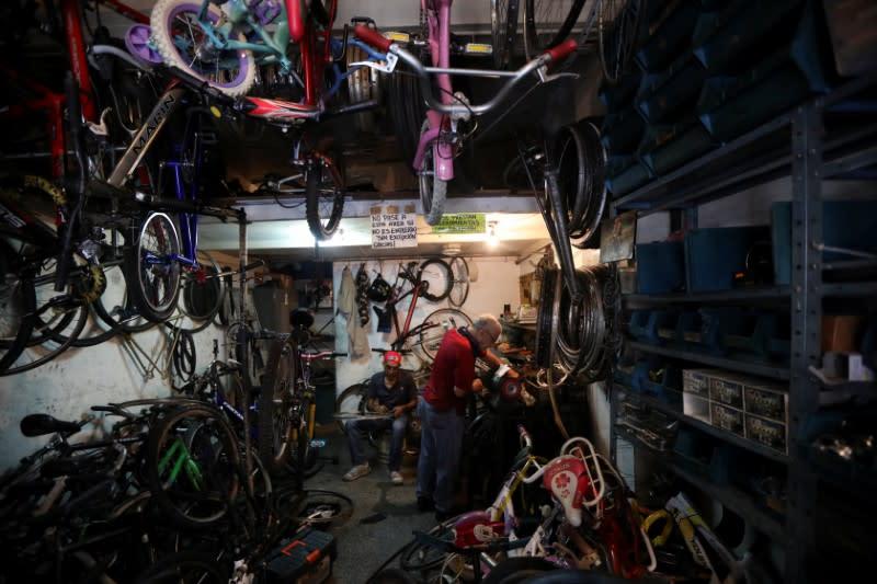 Bicycle repairman Pepe Segura works at his shop in Caracas