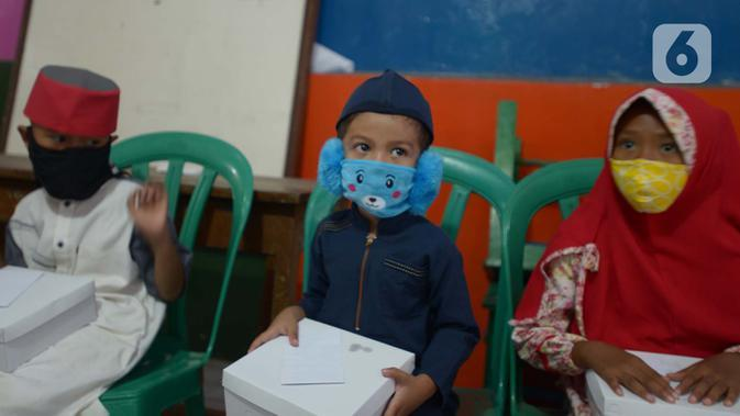 Anak-anak memakai masker di RW 11, Kelurahan Pondok Kopi, Jakarta, Jumat (18/9/2020). Di masa pandemi COVID-19, TNI dan Polri bersinergi mengimbau warga untuk mematuhi protokol kesehatan dengan memakai masker saat beraktivitas di luar rumah. (merdeka.com/Imam Buhori)