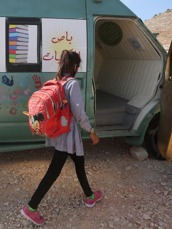 Seorang siswa Palestina berjalan menuju bus yang telah dialihfungsikan menjadi ruang kelas keliling di Khirbet Ibziq, dekat Kota Tubas, Tepi Barat, 8 Oktober 2020. Sebuah asosiasi lokal mengalihfungsikan sebuah bus menjadi perpustakaan dan ruang kelas keliling. (Xinhua/Ayman Nobani)