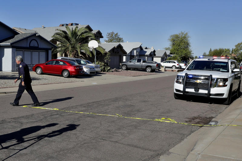 A Phoenix police officer lays out crime scene tape outside the scene of a deadly shooting early Monday, March 30, 2020, in Phoenix. Phoenix police say one of their commanders was killed and two other officers were wounded as they responded to a domestic dispute. Authorities say Cmdr. Greg Carnicle and officers were called to a home in the northern part of Phoenix Sunday night over a roommate dispute when the suspect refused to cooperate and shot them. The suspect was not identified and was pronounced dead at the scene. (AP Photo/Matt York)