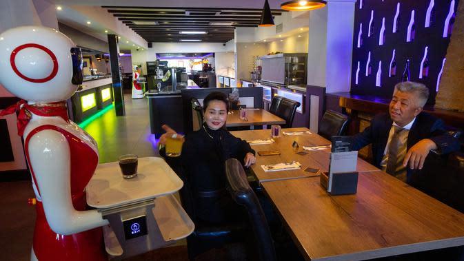 Pemilik restoran, Shu Lei Hu (kiri) dan suaminya Shao Song Hu menunjukkan penggunaan robot pengganti pelayan di restoran keluarga Royal Palace, Belanda, 27 Mei 2020. Satu hal yang pasti akan dilakukan robot berwarna merah-putih ini adalah memastikan aturan jarak sosial dihormati. (AP/Peter Dejong)