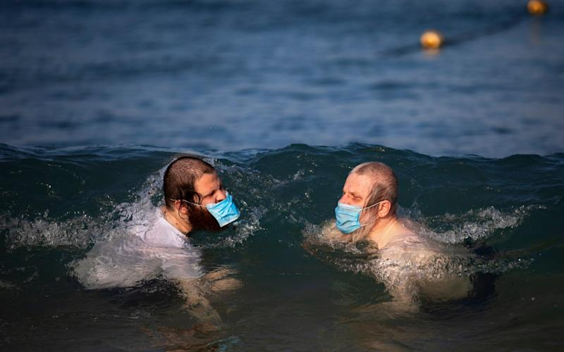 Ultra-orthodox Jewish men wearing protective face masks swim in the Mediterranean Sea, on a beach segregated for males three days a week, in Tel Aviv, Israel, - Oded Balilty/AP