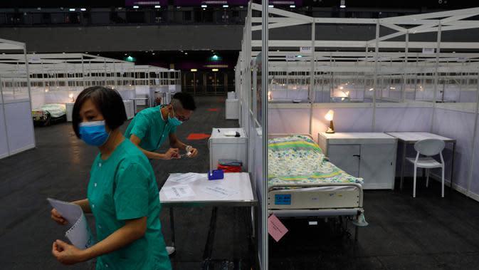 Pekerja medis membuat persiapan di rumah sakit lapangan sementara yang didirikan di Asia World Expo di Hong Kong, Sabtu (1/8/2020). Rumah sakit baru itu akan menerima pasien COVID-19 berusia antara 18 dan 60 tahun dengan sekitar 500 tempat tidur tersedia pada tahap pertama. (AP Photo/Kin Cheung)