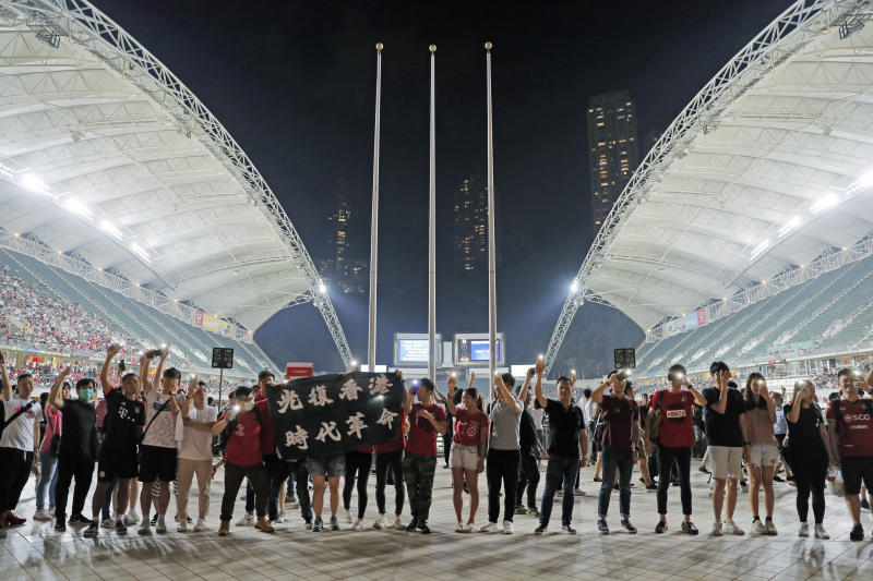 "Hong Kong soccer fans form human chain and chant banner reads ""Liberate Hong Kong, Revolution of Our Times."" during the FIFA World Cup Qatar 2022 and AFC Asian Cup 2023 Preliminary Joint Qualification Round 2 soccer match between Hong Kong and Iran, in Hong Kong, Tuesday, Sept. 10, 2019. The crowd broke out into ""Glory to Hong Kong,"" a song reflecting their campaign for more democratic freedoms in the semi-autonomous Chinese territory. (AP Photo/Kin Cheung)"
