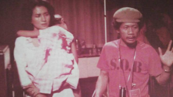 Ade Irawan saat memerankan Ibu Nasution dalam film Pengkhianatan G30S PKI sedang menggendong tokoh Ade Irma Suryani. (Instagram @dewiirawan13)