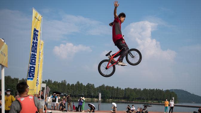Seorang pesepeda melompat ke Danau Timur menggunakan sepeda BMX dalam ajang tahunan festival lompat air (water jump) BMX di Wuhan, ibu kota Provinsi Hubei, China tengah, pada 22 Agustus 2020. (Xinhua/Xiao Yijiu)