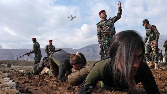 Pasukan perempuan Peshmerga merayap di tanah saat berlatihan dalam upacara kelulusan di Kota Soran, Irak, Rabu (12/2/2020). Latihan militer pasukan bersenjata Kurdi tersebut dilakukan sekitar 100 kilometer timur laut ibu kota otonomi wilayah Kurdi di Irak, Arbil. (SAFIN HAMED/AFP)