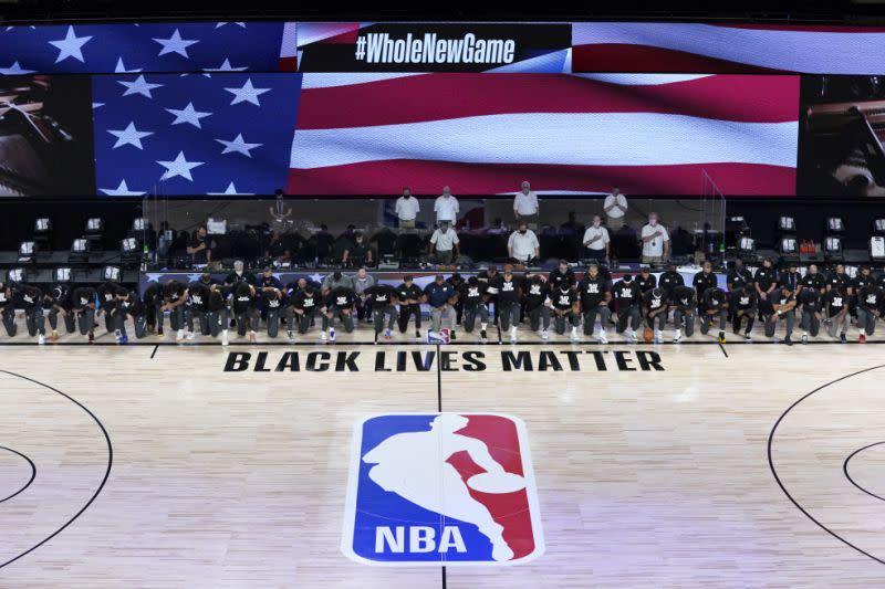 Pemain dan pelatih berlutut menjelang pertandingan pembukaan NBA
