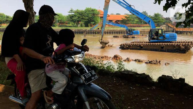 Pengendara motor melintas saat alat berat mengeruk lumpur di Setu Babakan, Jakarta, Selasa (30/6/2020). Pengerukan dilakukan guna mengembalikan kedalaman setu sehingga menambah daya tampungnya. (Liputan6.com/Immanuel Antonius)
