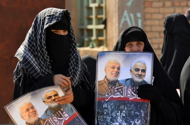 Iraqi women hold portraits of Iran's late top general Qasem Soleimani and Iraqi paramilitary commander Abu Mahdi al-Muhandis, killed in a US drone strike near Baghdad in January 2020