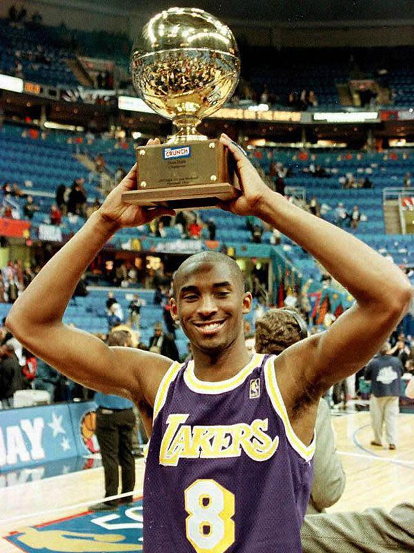Pemain Los Angeles Lakers, Kobe Bryant mengangkat piala setelah memenangkan kontes NBA Slam Dunk di Gund Arena di Cleveland, Ohio pada 8 Februari 1997. Bryant meninggal bersama putrinya yang berusia 13 tahun Gianna dalam kecelakaan helikopter di Calabasas. (AFP/Jeff Haynes)