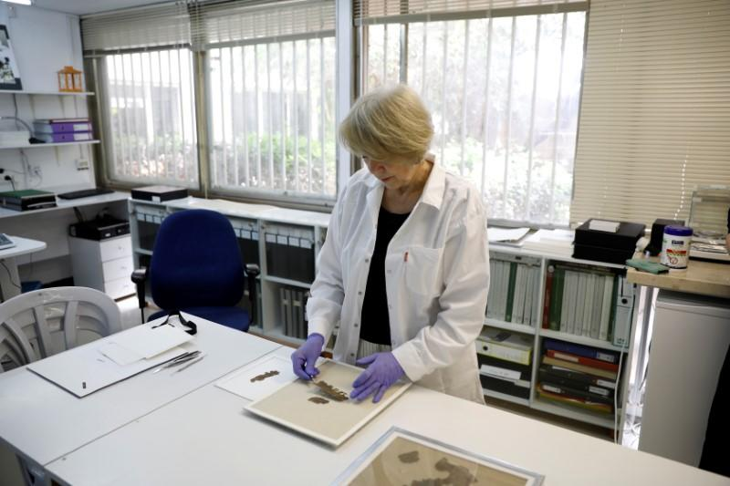 A conservator looks at a fragment from the Dead Sea Scrolls that underwent genetic sampling to shed light on the 2,000-year-old biblical trove, at the Israel Antiquities Authority laboratory in Jerusalem