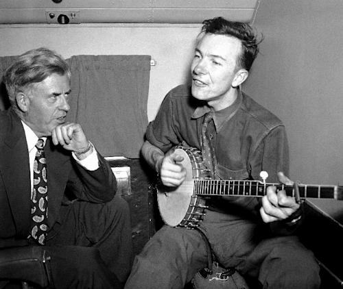 File-This Aug. 28, 1948, file photo shows Henry A. Wallace, listening to Pete Seeger, his banjo-playing singer, on a plane between Norfolk and Richmond, Va. The American troubadour, folk singer and activist Seeger died Monday Jan. 27, 2014, at age 94. (AP Photo/File)