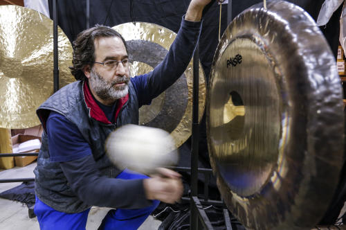 Andrew Borakove of Gongs Unlimited strikes a gong in his warehouse in Lincoln, Neb., Jan. 17, 2013. Borakove, a former comedy writer from California, switched occupations and moved to Lincoln, Neb., where he may be the world's pre-eminent gong dealer, selling hundreds of gongs, stands and gong-banging mallets a year. His clientele runs the gamut from car dealerships to Dubai casinos to rocker Roger Daltrey. (AP Photo/Nati Harnik)