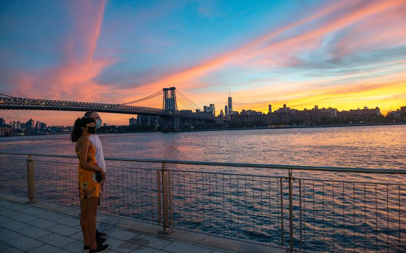 A couple wear facemasks as the sun sets in New York - Getty
