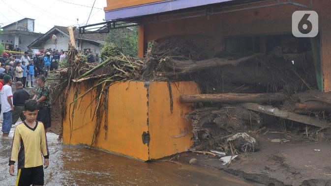 Seorang anak melintasi bangunan yang rusak usai banjir bandang melanda Kampung Cibuntu, Desa Pasawahan, Kecamatan Cicurug, Sukabumi, Jawa Barat, Selasa (22/9/2020). Data sementara puluhan bangunan rusak berat, 12 rumah hanyut, dan dua korban hilang masih dicari. (merdeka.com/Arie Basuki)