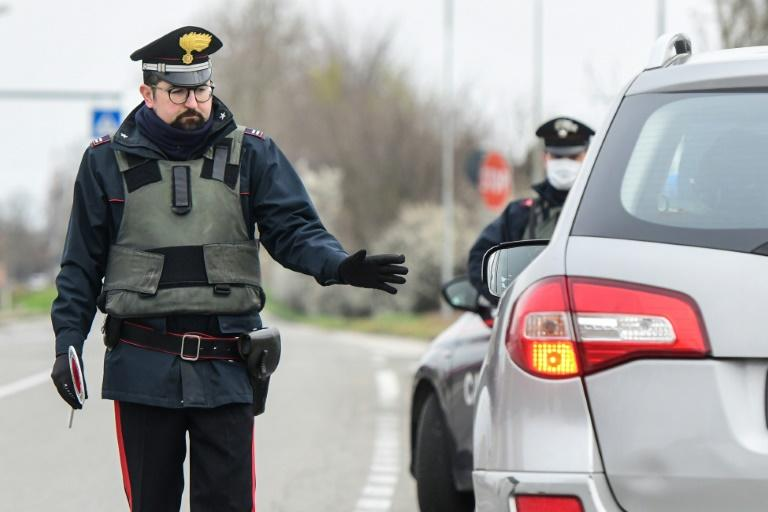 Italian police stop cars at a checkpoint between the quarantined provinces of Modena and Bologna