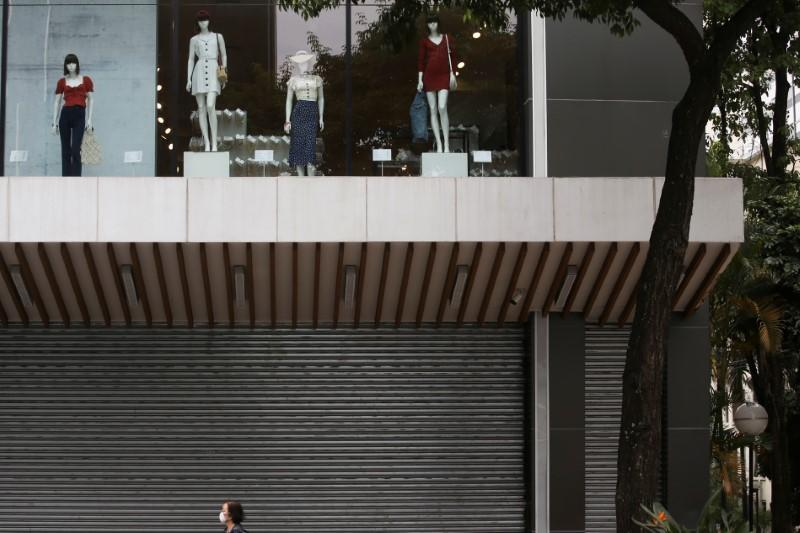 A woman wearing a face mask passes by a closed mall that reduced its opening hours amid the coronavirus disease (COVID-19) outbreak in Sao Paulo