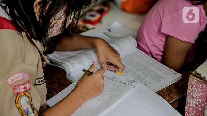 Seorang murid SD mengikuti kegiatan pembelajaran jarak jauh di sebuah pos keamanan RT 003 RW 006 Bendungan Hilir, Tanah Abang, Jakarta, Jumat (14/8/2020). Selama Covid-19, anak-anak memanfaatkan televisi yang ada untuk mengikuti pelajaran sekolah yang disiarkan TVRI. (Liputan6.com/Faizal Fanani)