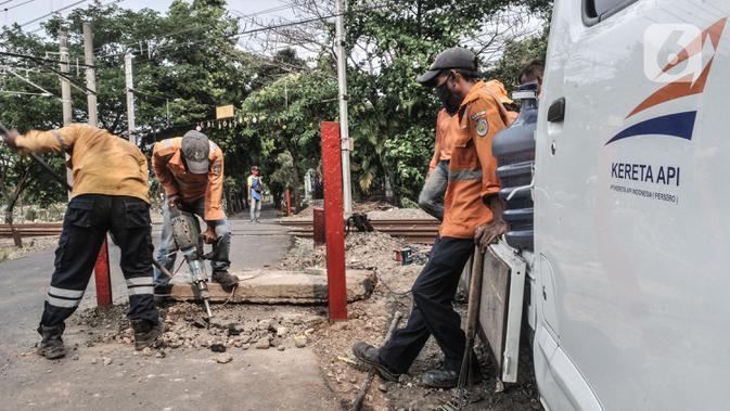 Pekerja PT KAI menyelesaikan pemasangan pembatas jalan di perlintasan kereta tanpa palang pintu di kawasan TPU Tanah Kusir, Jakarta, Kamis (17/9/2020). Pemasangan pembatas jalan dilakukan untuk mencegah kecelakaan kendaraan yang sering terjadi di kawasan tersebut. (merdeka.com/Iqbal S. Nugroho)