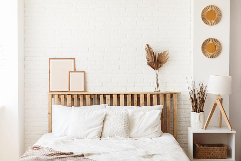 Wooden headboard with dry gold palm leaves in a glass vase and two photo frames on it. Stylish trendy decoration with copy space.