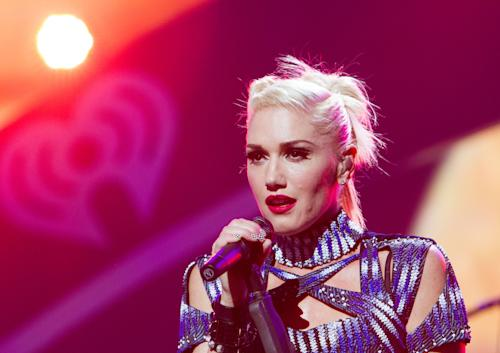 """FILE - This Sept. 21, 2012 file photo originally released by Clear Channel shows Gwen Stefani of No Doubt performing at the 2012 iHeartRadio Music Festival at the MGM Grand Garden Arena in Las Vegas, Nev. No Doubt has pulled its new cowboys and Indians-themed music video and is apologizing to Native Americans and others who were offended by the clip. The band posted on its website Saturday, Nov. 3, that the video for """"Looking Hot"""" was """"never to offend, hurt or trivialize Native American people."""" The video features Gwen Stefani and bandmate Tony Kanal dressed in traditional Native American clothes, while Adrian Young and Tom Dumont are in cowboy get-ups with guns. Stefani also rides and horse and sings in a tepee in the clip, which includes a fire-burning dance scene with others dressed in Native American clothes. (AP Photo/Clear Channel, Andrew Swartz)"""